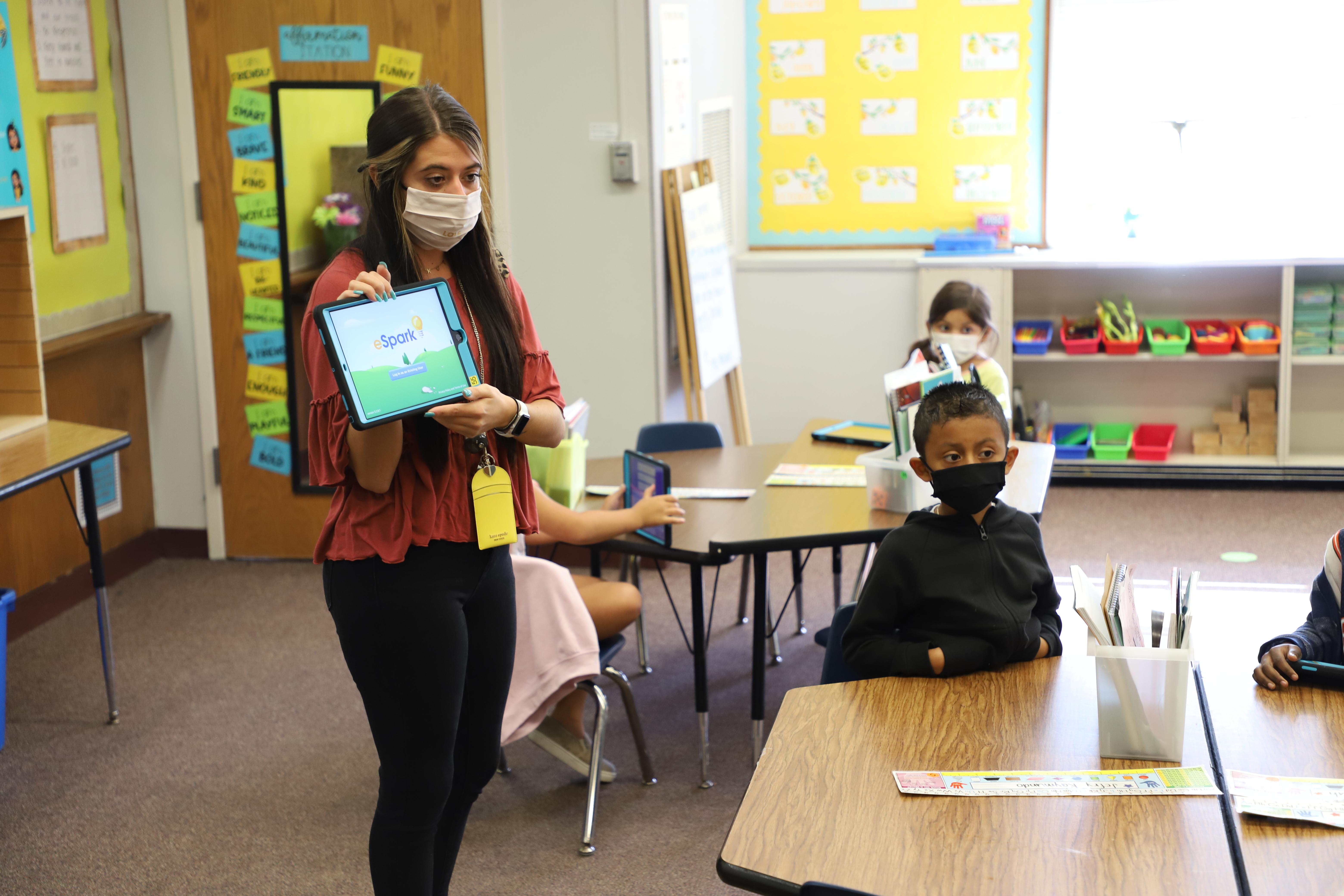 Dakota Wesslund holds a tablet while Jefry Raymundo-Chumux looks toward the camera in Wesslund's first-grade classroom at Mockingbird Elementary. (Jim Frederick/Ralston Public Schools)