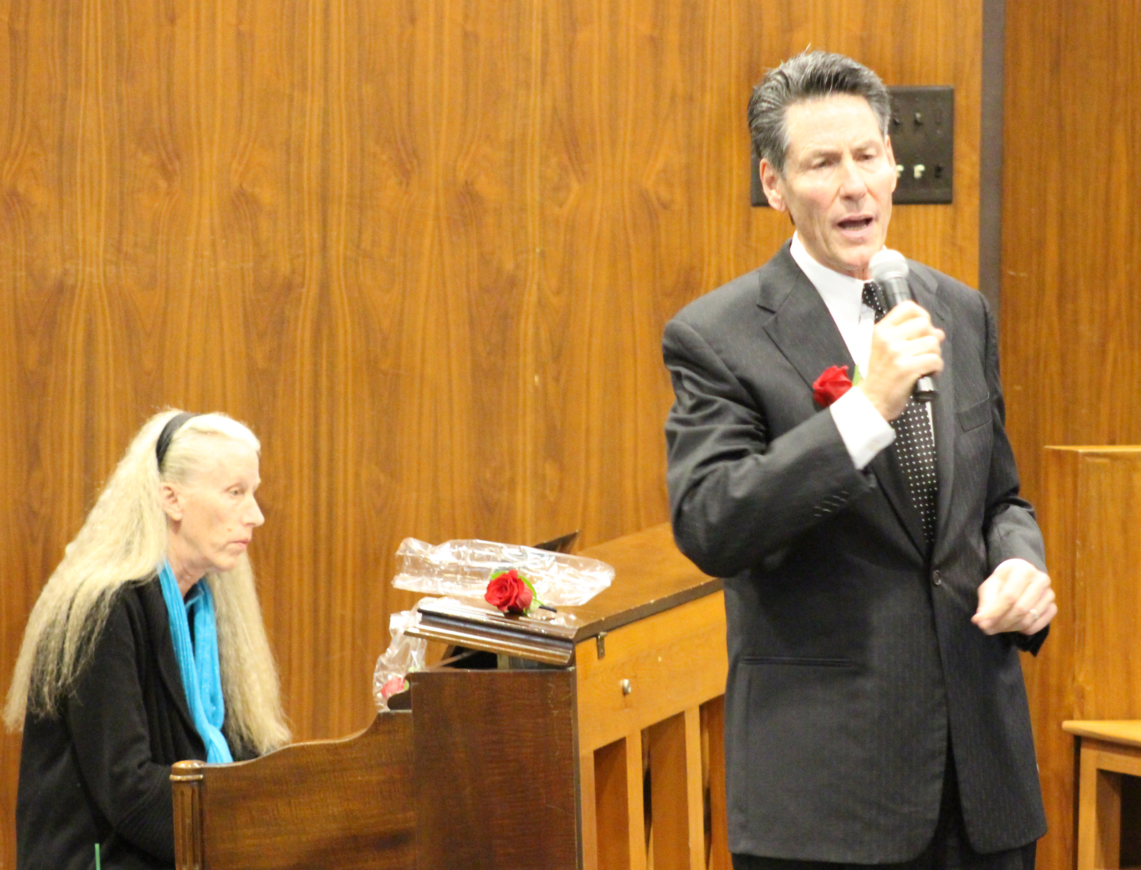 "Thomas J. Shomaker of Sodoro Daly Shomaker, right, sings ""Shepard Me, O God"" with accompaniment by Peg Lacy on the piano during the Omaha Bar Association's annual Memorial Day Program in the legislative chamber of the Omaha-Douglas Civic Center on May 10, 2019. (Photo by Scott Stewart)"