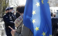 A woman holding a European Union flag protests outside the Constitutional Tribunal in Warsaw, Poland, on Wednesday April 28, 2021. The constitutional court was to rule on Wednesday on whether Polish or European Union law has primacy in the country. It delayed its proceedings until May 13. Some Poles fear that if the court rules that Polish law has primacy it could badly hurt the country's future relationship with the rest of the bloc. (AP)