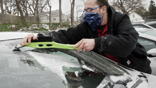 David Larrick wears a home-made mask to protect himself against the coronavirus as he clears ice and snow off of his windshield at a parking lot in Omaha, Friday, April 3, 2020. An overnight storm brought snow, freezing rain and sleet to the area. (AP Photo/Nati Harnik)