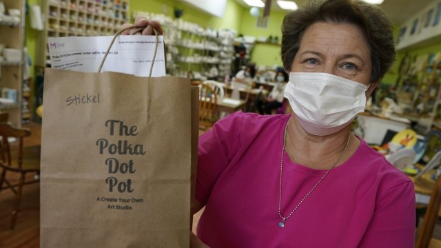 Polka Dot Pot owner Emily Rhodes holds a take home bag at her shop in the Old Town area Wednesday Oct. 7, 2020, in Winchester, Va. The viral pandemic has hammered small businesses across the United States, an alarming trend for an economy that's trying to rebound from the deepest, fastest recession in U.S. history. Small companies are struggling in Winchester, a city of 28,000 that works hard to promote and preserve local enterprises. (AP)